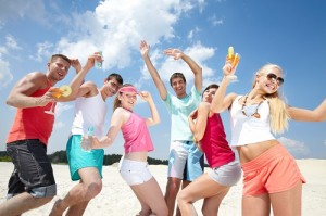 Six friends dancing on beach with cocktails